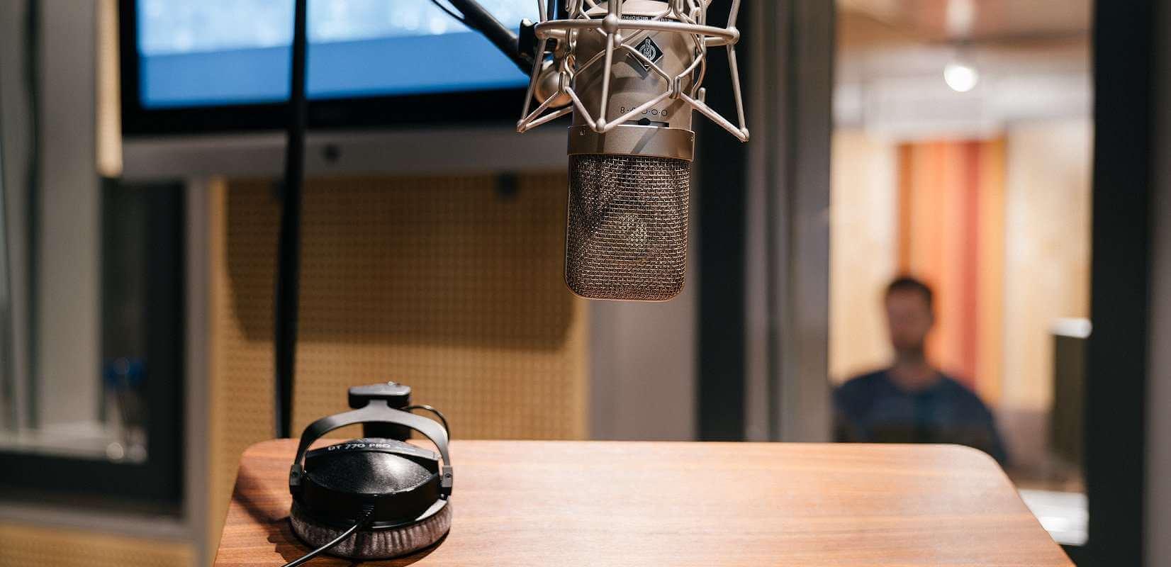 Blick aus dem Aufnahmeraum in das Tonstudio mit Studiomikrofon und Kopfhörer